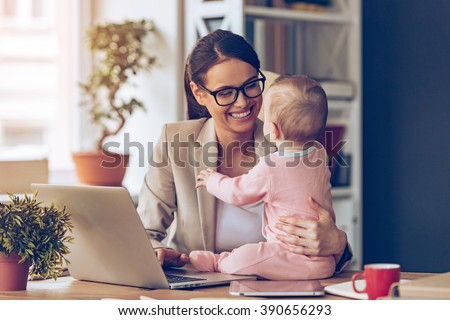 Working together is so fun! Cheerful young beautiful businesswoman looking at her baby girl with smile while sitting at her working place - stock photo