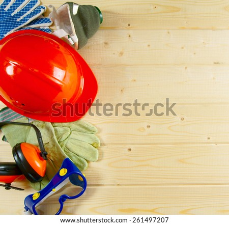 Working tools. A helmet, ear-phones, glasses protective and other tool on a wooden background. - stock photo