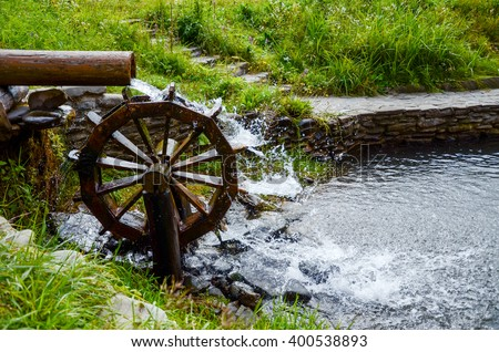 Working watermill wheel with falling water in the village - stock photo