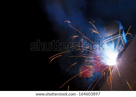Working welder on black background with copy space - stock photo