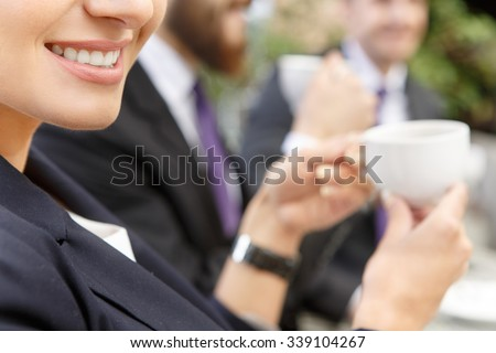 Working with a smile on her face. Cropped shot of a woman smiling while having a coffee during business meeting in the cafe  - stock photo