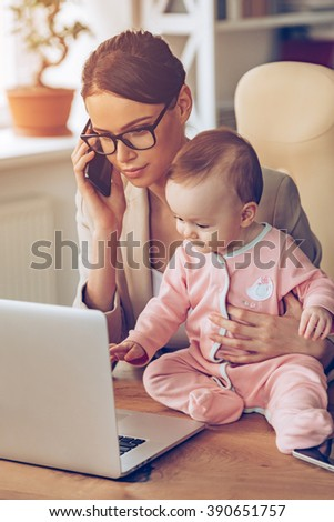Working with baby. Young beautiful businesswoman talking on mobile phone and looking at laptop while sitting with her baby girl at her working place - stock photo