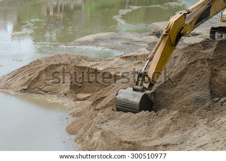 Working with excavator digging sand at the river site in drought, Thailand. - stock photo