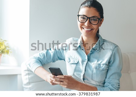 Working with joy. Beautiful young cheerful woman in glasses using her smart phone and looking at camera with smile while sitting on the couch near windowsill - stock photo