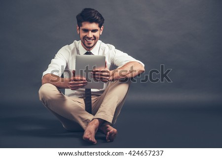 Working with pleasure. Full length of confident young handsome man using his digital tablet with smile while sitting on the floor against grey background - stock photo