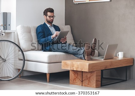 Working with pleasure. Handsome young man keeping legs on table and working with touchpad while sitting on the couch in office - stock photo
