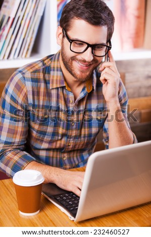 Working with pleasure. Top view of happy young man talking on the mobile phone and looking at his laptop while sitting at the desk with bookshelf in the background - stock photo