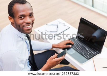 Working with smile. Top view of young African man in formalwear working on laptop and smiling while sitting at his working place - stock photo