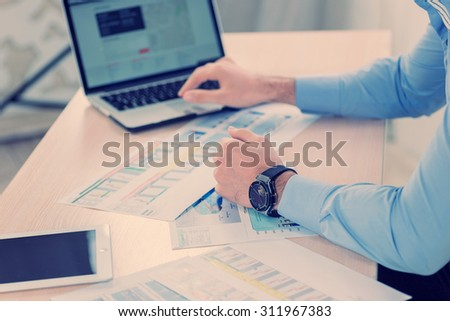 Working with the notebook. Confident businessman working at his laptop. Close-up view of the hands of a businessman in the office of the table in the formal wear. - stock photo