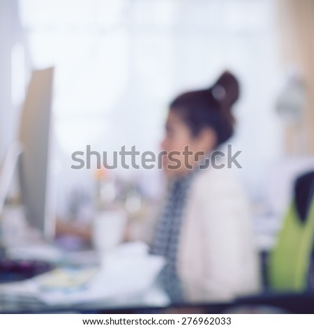 working woman with computer, image blur background - stock photo