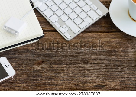 Working wooden table with empty space and frame of devices - stock photo