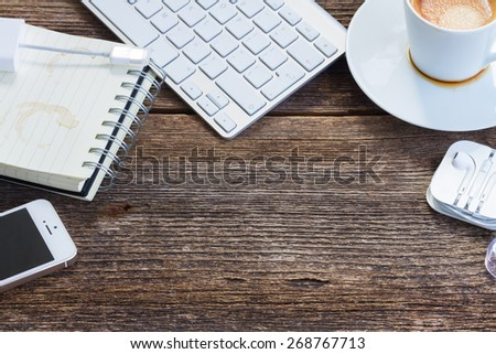 Working wooden table with empty space and frame of gadgets - stock photo