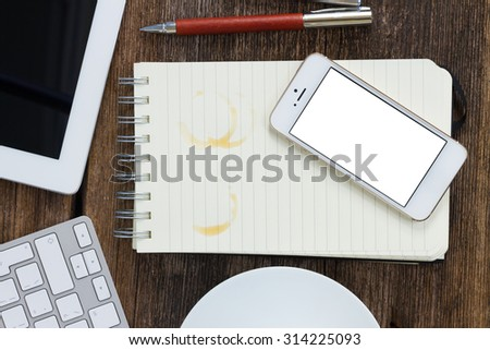 Working wooden table with notebook and phone, top view - stock photo
