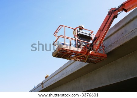 Workman inspects new bridge concrete from a man lift - stock photo