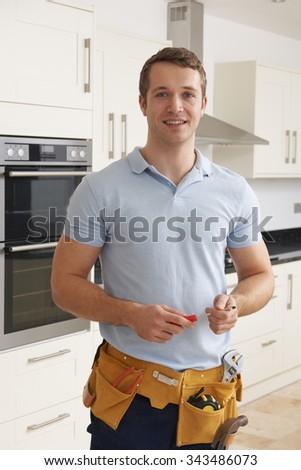 Workman Installing Luxury Fitted Kitchen - stock photo