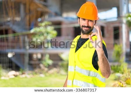 Workman making Ok sign on unfocused background - stock photo