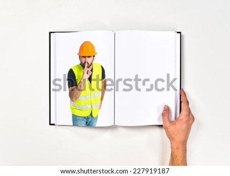 Workman making silence gesture printed on book - stock photo