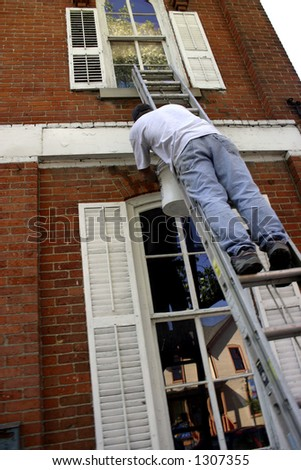 Workman painting the front of a building - stock photo