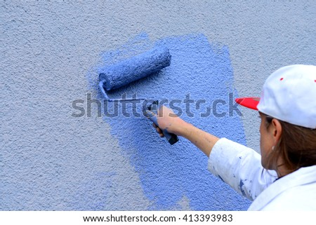 workman painting the wall with paint roller  - stock photo