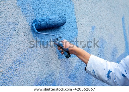workman painting the wall with paint roller in blue - stock photo