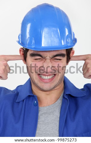 workman putting fingers in his ears to block out noise - stock photo