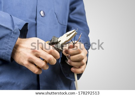 Workman repairing an electrical cable with a pair of pliers. On grey background with copyspace. - stock photo