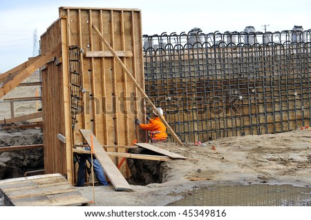 Workman ties reinforcing steel bars to wooden forms prior to pouring concrete on construction project - stock photo