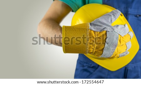 Workman wearing a protective glove holding a yellow hardhat or safety helmet conceptual of a builder, construction worker, tradesman or manual labourer - stock photo