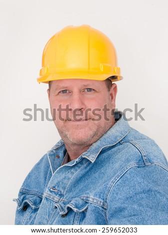 Workman wearing hardhat and jean jacket.  - stock photo