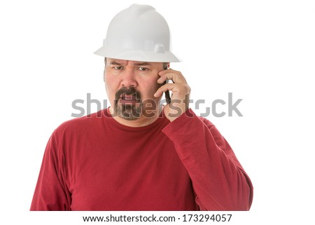 Workman with a goatee beard wearing a hardhat listening to a call on his mobile phone with a look of shocked confusion isolated on white - stock photo