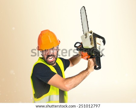 Workman with chainsaw over ocher background - stock photo