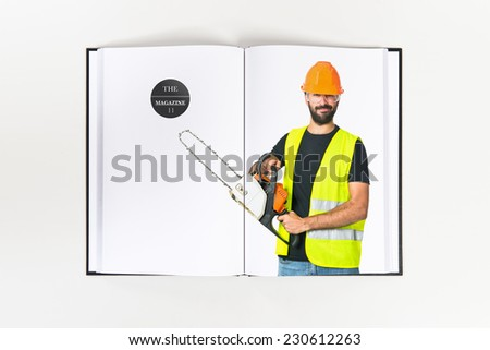 Workman with chainsaw printed on book - stock photo