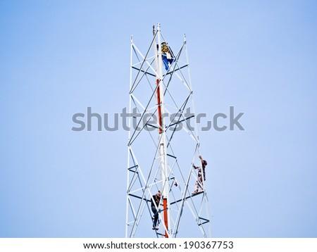 workmen  climbing antenna tower - stock photo