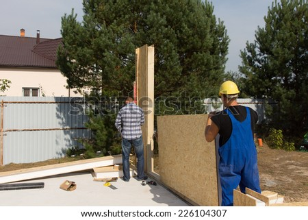Workmen erecting wall insulation panels clad in wooden boards as they work on a new build house construction site - stock photo