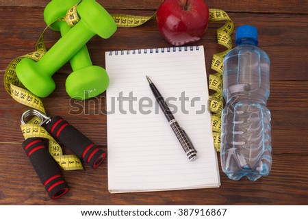 Workout and fitness dieting copy space diary. Healthy lifestyle concept. Apple, dumbbell, water, expander hand and measuring tape on rustic wooden table.