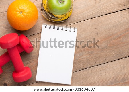 Workout and fitness dieting copy space diary. Healthy lifestyle concept. Orange, apple, dumbbell and measuring tape on rustic wooden table. View from above - stock photo