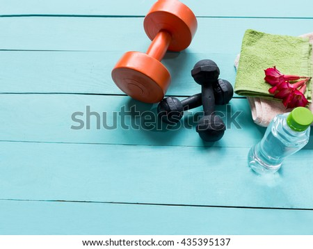 Workout and fitness dieting- Healthy lifestyle concept and other stuff Dumbbell, water, on the blue wooden background - stock photo