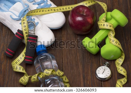 Workout and fitness dieting. Healthy lifestyle concept. Apple, dumbbell, water, expander hand, stopwatch and measuring tape on rustic wooden table. - stock photo