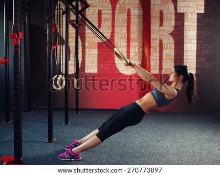 "Workout on rings. Athletic young brunette woman in gray sportswear, trains on the rings in the gym with red wall on which is written the word ""sport"". View from the side - stock photo"