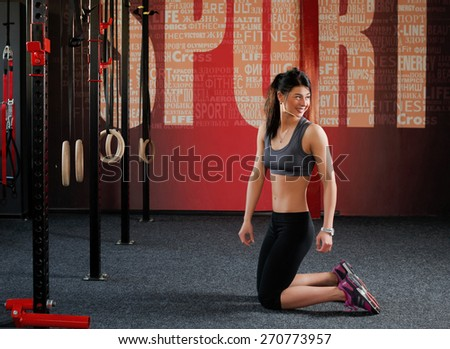 Workout on rings. Fit woman training session on the rings in the gym. Attractive muscular woman, caucasian appearance, brunette is kneeling in the gym and looking to the side - stock photo