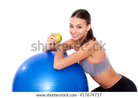 Workout snack. Portrait of a young woman sitting next to her fitness ball and eating an apple. - stock photo