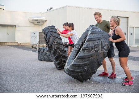 Workout team flipping tires outdoor - stock photo
