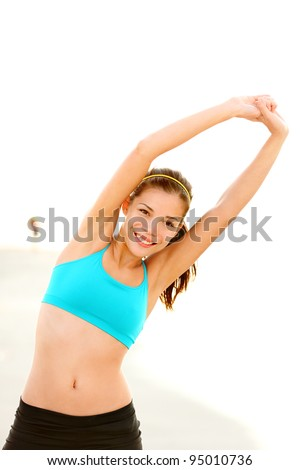 Workout woman training on beach. Fit fitness model stretching after running outside. Beautiful young mixed race Asian Caucasian female fitness model smiling happy. - stock photo