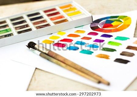 Workplace artist - paper, paint, brushes, color wheel.  - stock photo
