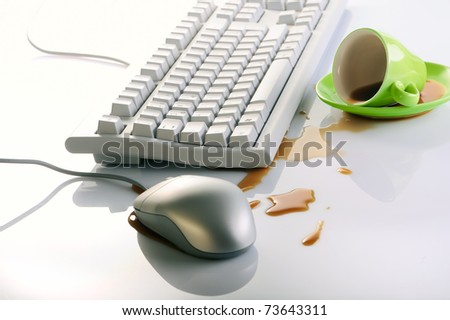 Workplace - computer keyboard and mouse, spilled cup of coffee on the table - stock photo