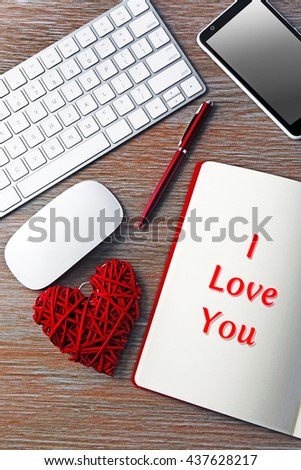 Workplace decorated with Valentine's heart and text I Love You, top view - stock photo