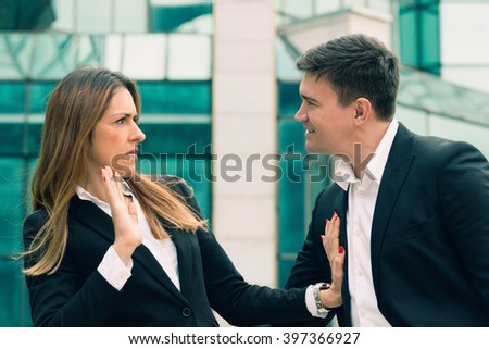 Workplace harassment - young business woman stopping aggressive colleague - stock photo