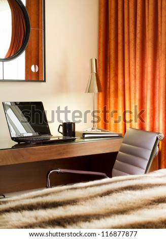 Workplace in room with laptop, notebook, lamp and a cup of coffee on the table - stock photo