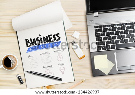 Workplace, laptop and notepad with hand drawn business strategy. - stock photo