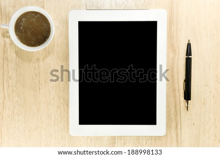 Workplace with blank digital tablet, pen and cup of coffee on work table top view - stock photo
